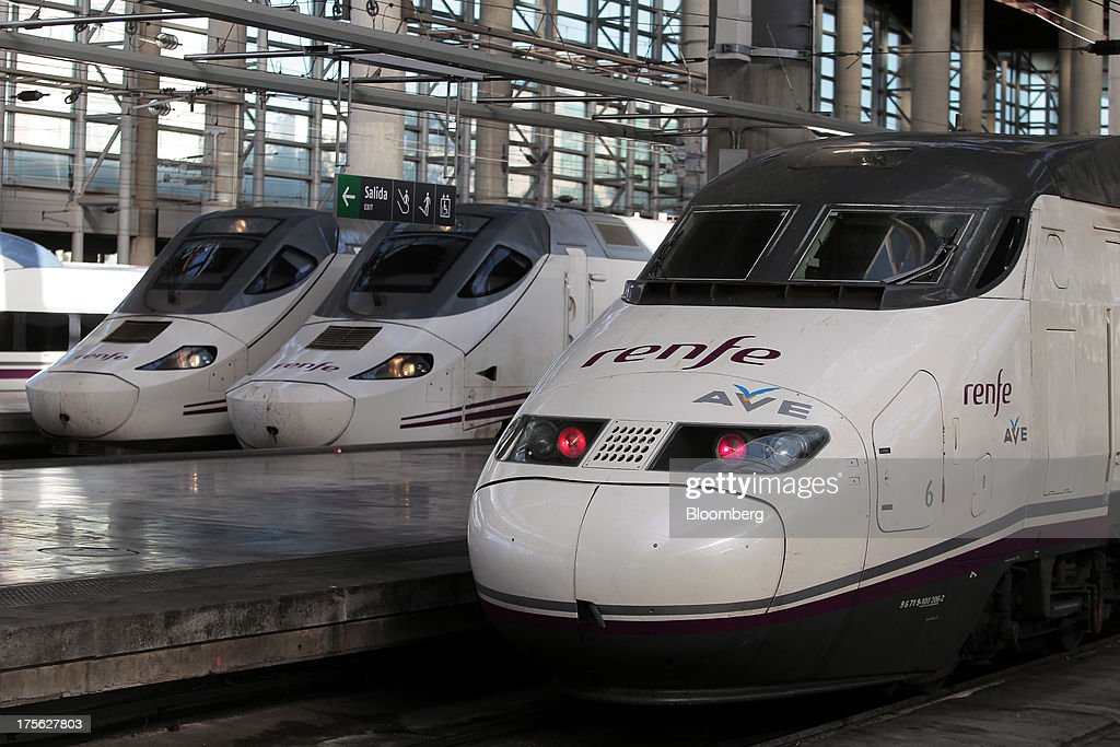 Alta Velocidad Espanola (AVE) high-speed trains operated by Renfe Operadora SC sit beside platforms at Atocha train station in Madrid, Spain, on Saturday, Aug. 3, 2013. Spain's state-owned rail operator Renfe plans to cut almost 500 jobs, or 4% of staff, as early as this year, ABC reports, citing comments by Public Works Minister Ana Pastor. Photographer: Antonio Heredia/Bloomberg via Getty Images