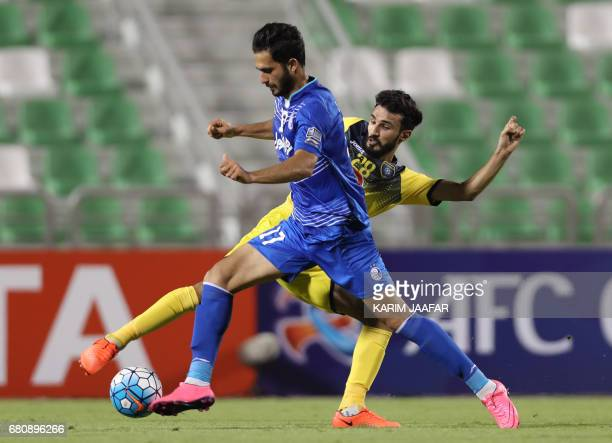 CORRECTION AlTaawoun's defender Abdullah Haif alShammari tackles Esteghlal's forward Ghotbani Ali during their Asian Champions League football match...