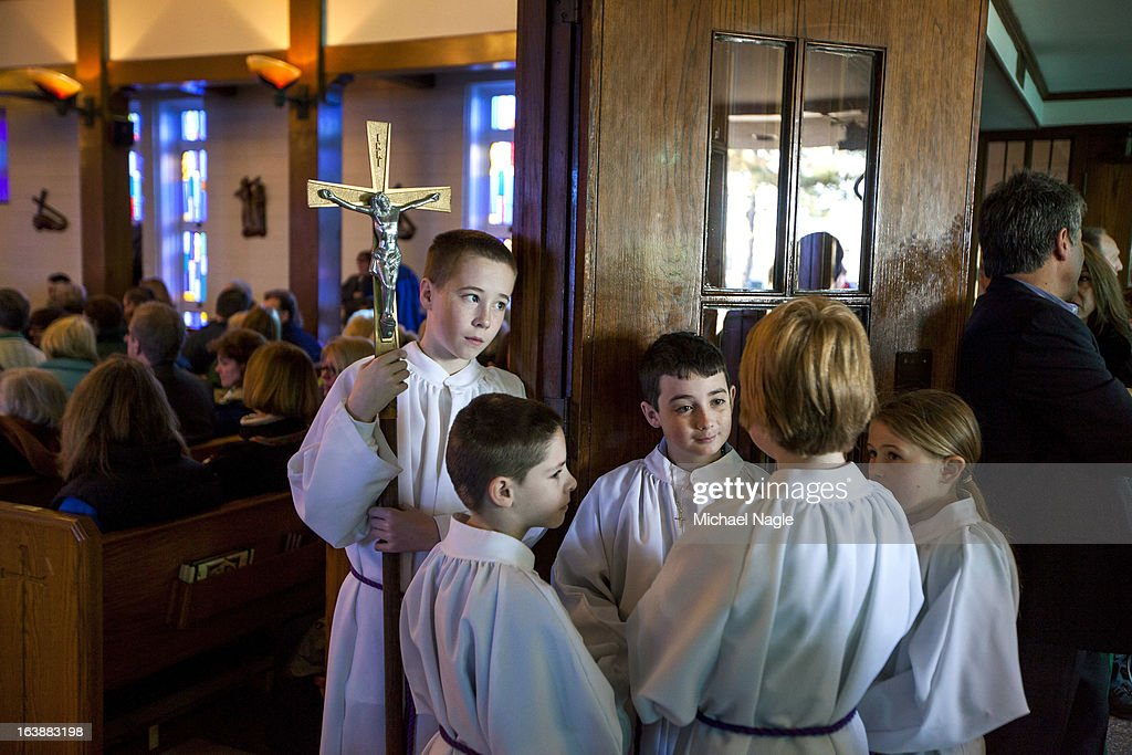 Alter boys and girls chat with one-another before the arrival of Irish Prime Minister Enda Kenny for Saint Patrick's Day Mass at St. Thomas More Church on March 17, 2013 in the Breezy Point neighborhood in the Queens borough of New York City. Breezy Point, home to many residents with Irish ancestry, was devastated by Superstorm Sandy in October 2012.