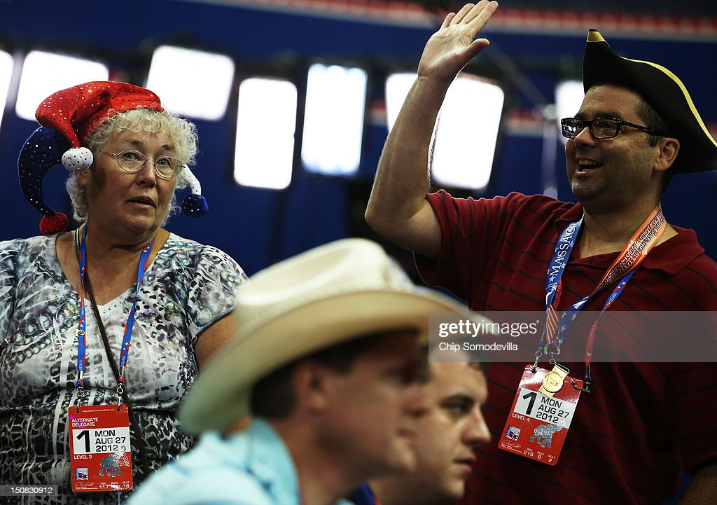 Alternate delegate Karen Skrill (L) of Randolph, VT wears a jester hat, as blogger Tom Moor (R) of Boston, MA wears a tri-corner hat as alternate delegate John Burgin (foreground) wears a cowboy hat on the arena floor before the start of the abbreviated first day of the Republican National Convention at the Tampa Bay Times Forum on August 27, 2012 in Tampa, Florida. The RNC is scheduled to convene today, but will hold its first full session tomorrow after being delayed due to Tropical Storm Isaac.