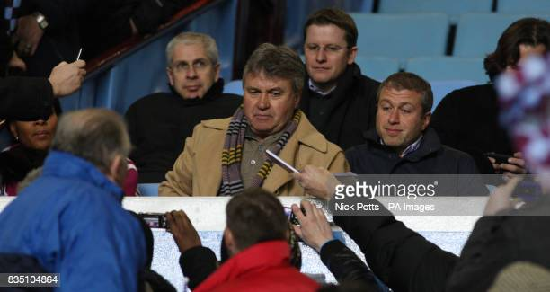 **Alternative Crop** Chelsea's new temporary head coach Guus Hiddink with club owner Roman Abramovich sign autographs in the stand