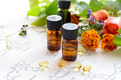 essential oils and supplement with herbs, marigold and rose flowers on science sheet  in white background