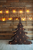 Alternative wooden christmas tree. A handmade New Year tree with light bulb on the floor on wooden background. Loft interior. Copy space.
