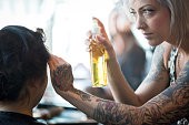 A serious, attractive young woman hair stylist with unique style (tattoos, piercings, platinum hair, leopard skin clothing) uses hairspray to complete a client's hairstyle – a trendy, braided updo for