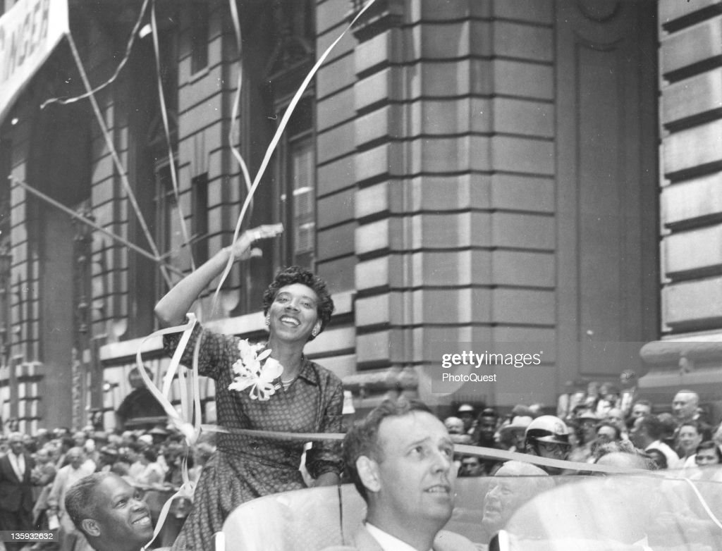Althea Gibson, the first African American to become tennis champion of the world by winning the Wimbledon match in England, waves from an open car during the parade up Broadway in the City's official tribute to her, New York, New York, July 11, 1957.