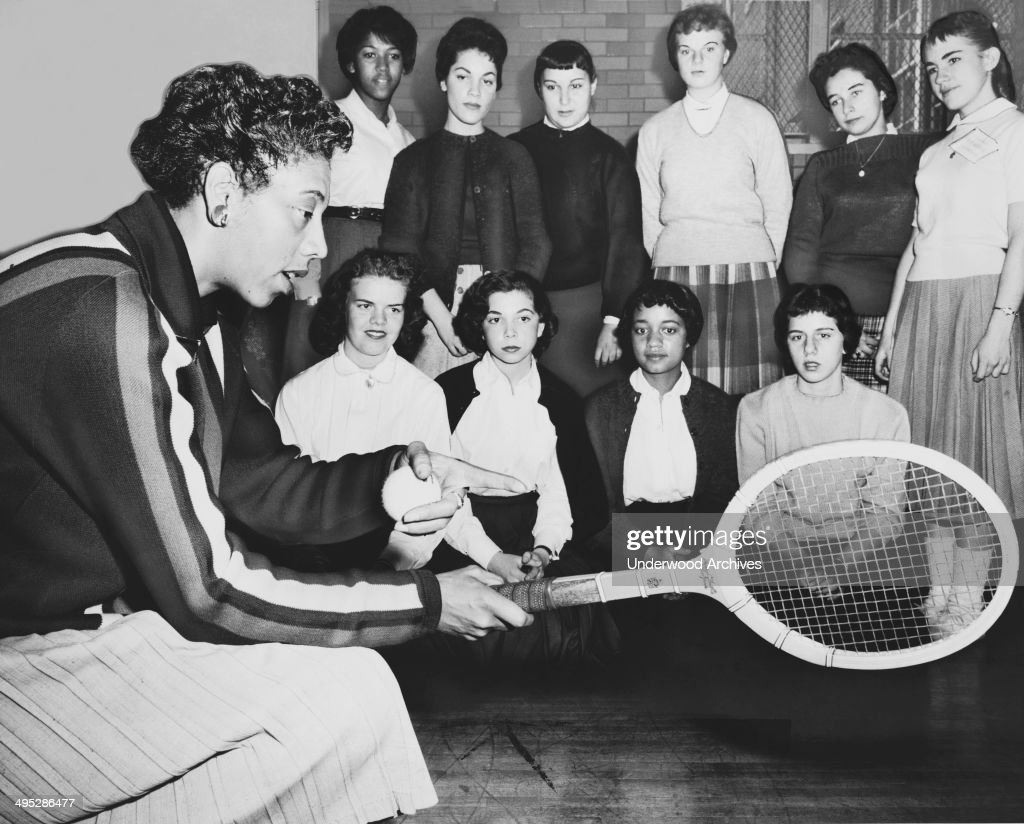 Althea Gibson, US and Wimbledon tennis champion, gives some pointers on the game to students attending a tennis clinic at Midwood High School in Brooklyn, New York, New York, December 1957.
