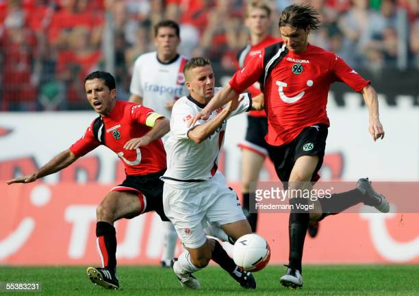 Altin Lala and Thomas Brdaric of Hannover tussels for the ball with Benjamin Kohler of Frankfurt during the Bundesliga match between Hanover 96 and...
