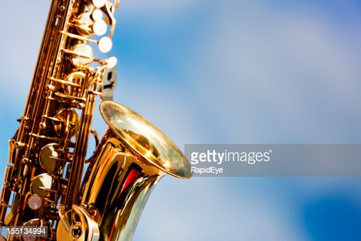 Alto sax close up against sky with scattered clouds