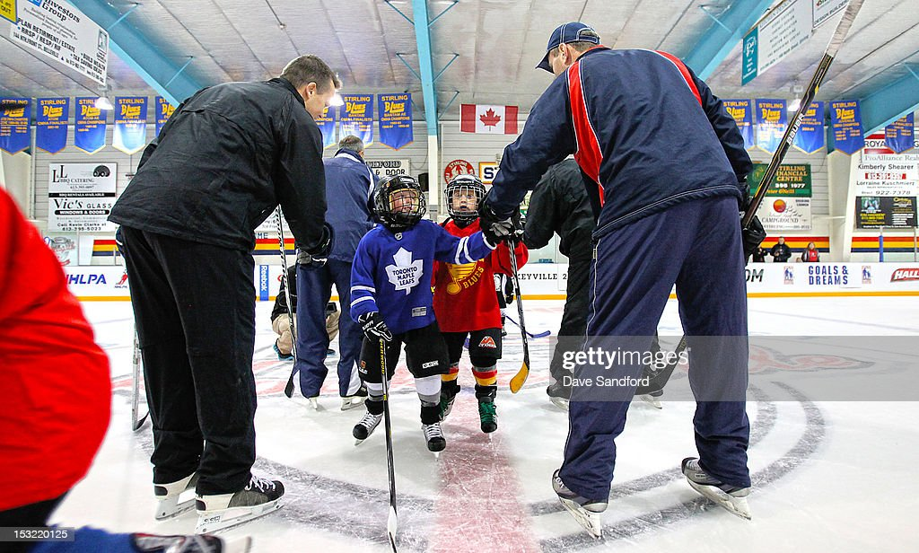 Alumni Mike Gaul and Tom Fergus high-five with kids taking part in a hockey clinic held at the Stirling and District Recreation Centre during Kraft Hockeyville Day 2 on October 1, 2012 in Stirling, Ontario, Canada.
