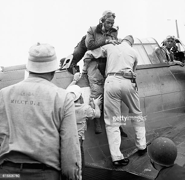 Alva Parker is helped from his Douglas Dauntless on board the USS Saratoga after receiving shrapnel wounds during a raid on Rabaul November 5 1943