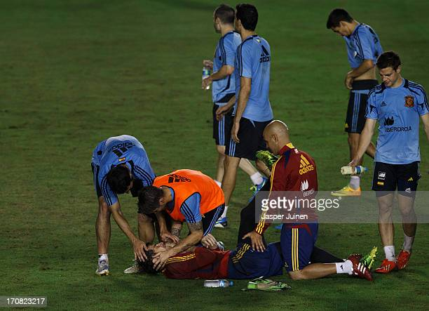 Alvaro Arbeloa and Sergio Ramos of Spain joke with goalkeeper Iker Casillas laying on the pitch during a training session ahead of his team's FIFA...