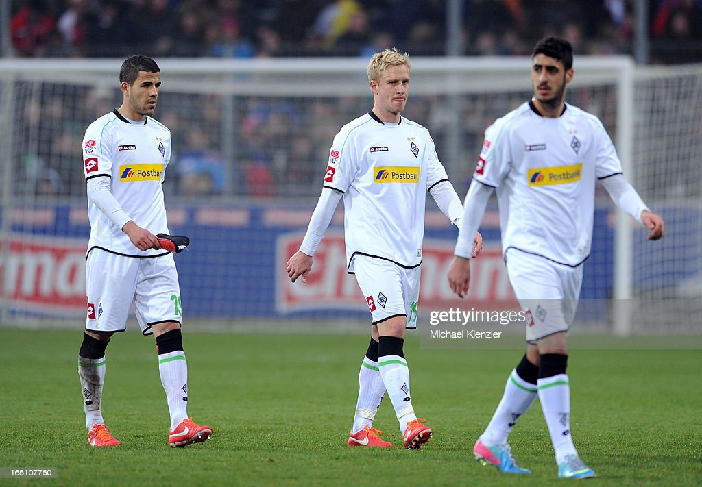 Alvaro Dominguez Santo, Mike Hanke and Tolga Cigerci (L-R) of Borussia Moenchengladbach leaving field after the Bundesliga match between SC Freiburg and VfL Borussia Moenchengladbach at MAGE SOLAR Stadium on March 30, 2013 in Freiburg, Germany.