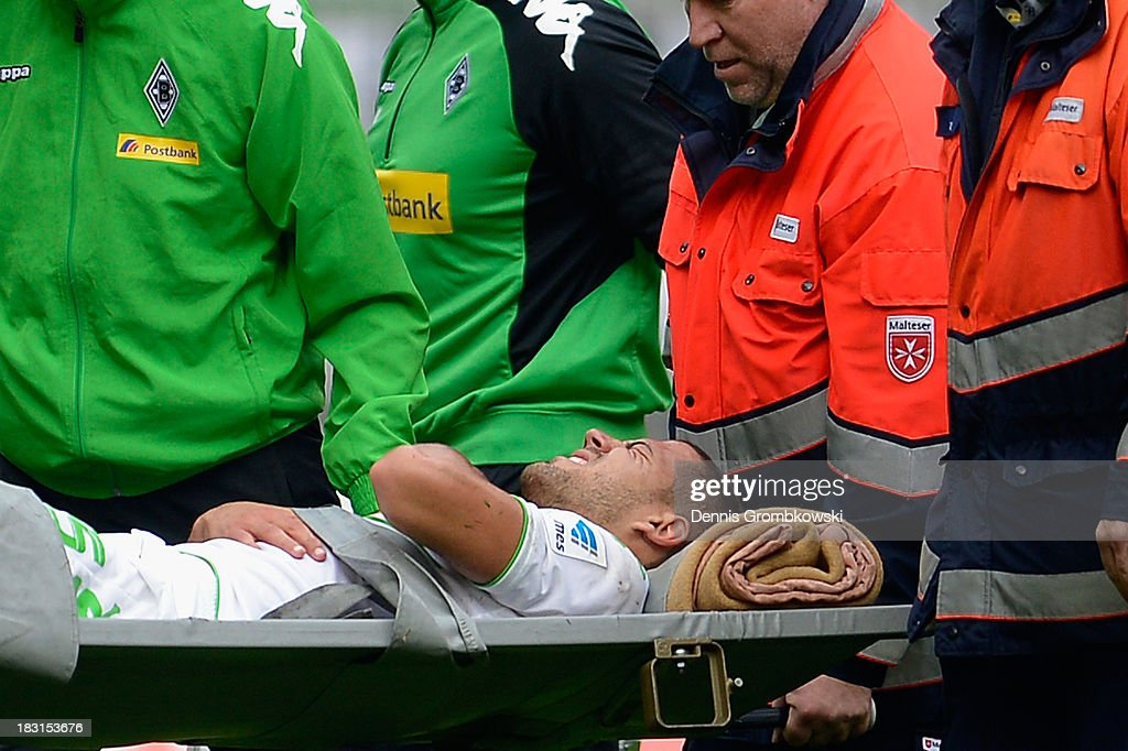 Alvaro Dominguez Soto of Borussia Moenchengladbach is brought off the pitch on a stretcher after suffering an injury during the Bundesliga match between Borussia Moenchengladbach and Borussia Dortmund at Borussia-Park on October 5, 2013 in Moenchengladbach, Germany.