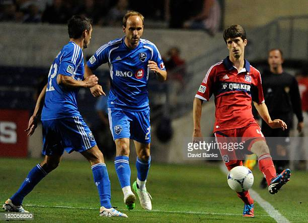 Alvaro Fernandez of the Chicago Fire is defended by Justin Mapp Montreal Impact and Davy Arnaud in an MLS match on September 15 2012 at Toyota Park...