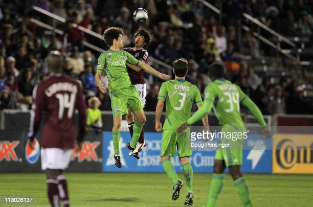 Alvaro Fernandez of the Seattle Sounders FC and Kosuke Kimura of the Colorado Rapids vie for a head ball as Omar Cummings of the Colorado Rapids and...