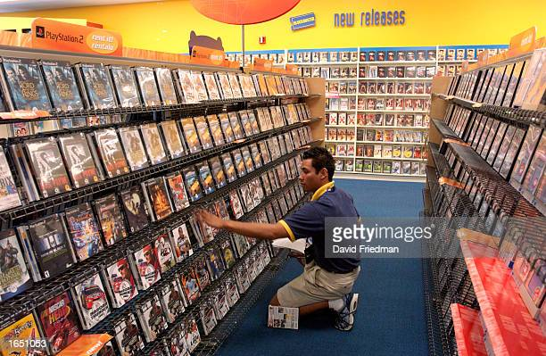 Alvaro Gutierrez reshelves PlayStation 2 games at a Blockbuster Video store November 19 2002 in the Little Havana section of Miami Florida...