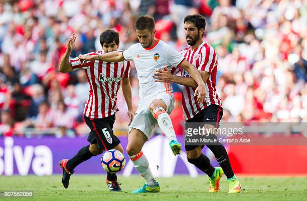 Alvaro Medran of Valencia CF competes for the ball with Raul Garcia of Athletic Club during the La Liga match between Athletic Club Bilbao and...