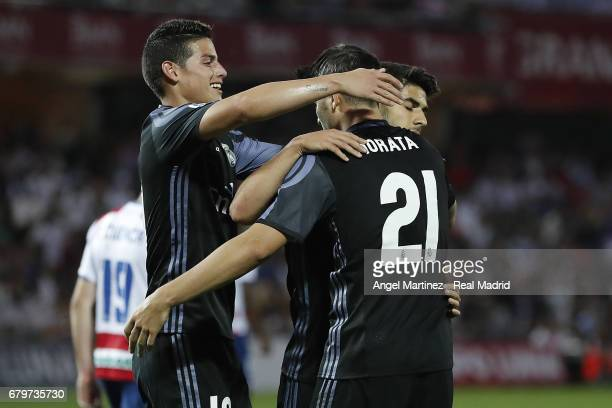 Alvaro Morata of Real Madrid celebrates with James Rodriguez and Marco Asensio after scoring their team's fourth goal during the La Liga match...