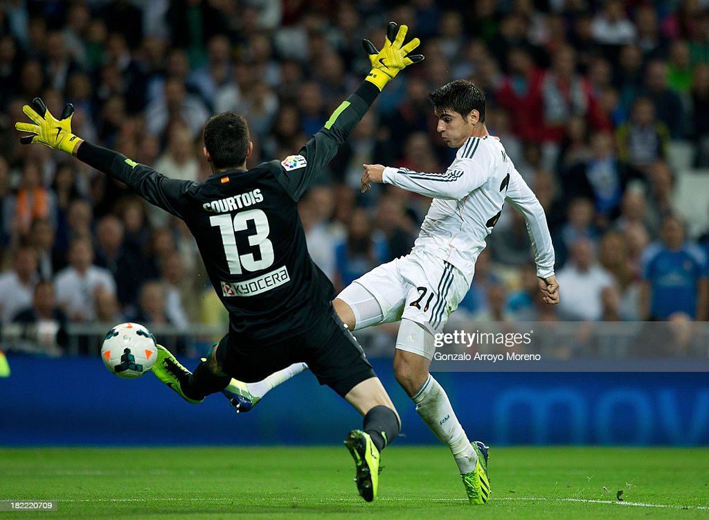 Alvaro Morata of Real Madrid CF strikes the ball past goalkeeper Thibaut Courtois of Atletico de Madrid during the La Liga match between Real Madrid CF and Club Atletico de Madrid at Estadio Santiago Bernabeu on September 28, 2013 in Madrid, Spain.