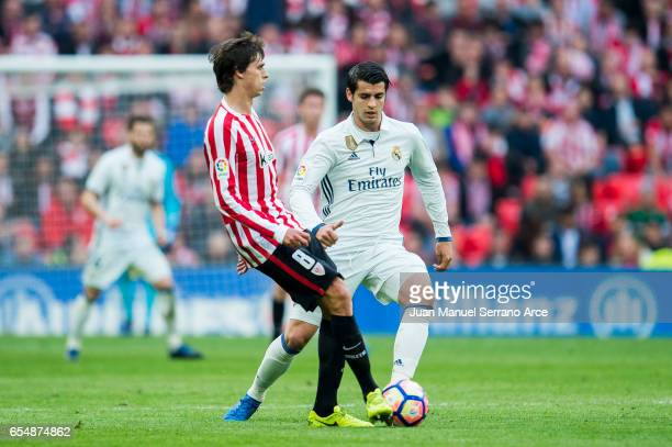 Alvaro Morata of Real Madrid competes for the ball with Ander Iturraspe of Athletic Club during the La Liga match between Athletic Club Bilbao and...