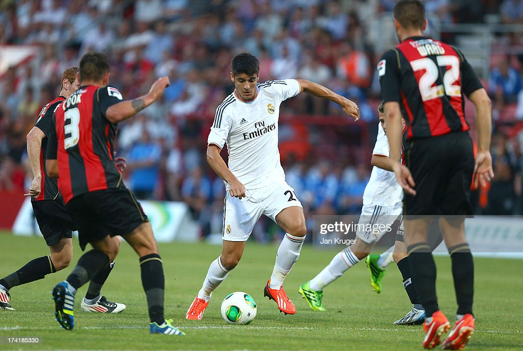 Alvaro Morata of Real Madrid (c) controls the ball from Steve Cook of AFC Bournemouth during a pre season friendly match between AFC Bournemouth and Real Madrid at Goldsands Stadium on July 21, 2013 in Bournemouth, England.
