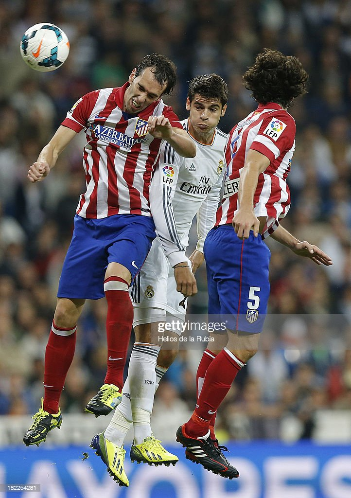 Alvaro Morata (C) of Real Madrid heads the ball against Diego Godín and Tiago Mendes of Atletico de Madrid during the La Liga match between Real Madrid and Club Atletico de Madrid at Estadio Santiago Bernabeu on September 28, 2013 in Madrid, Spain.