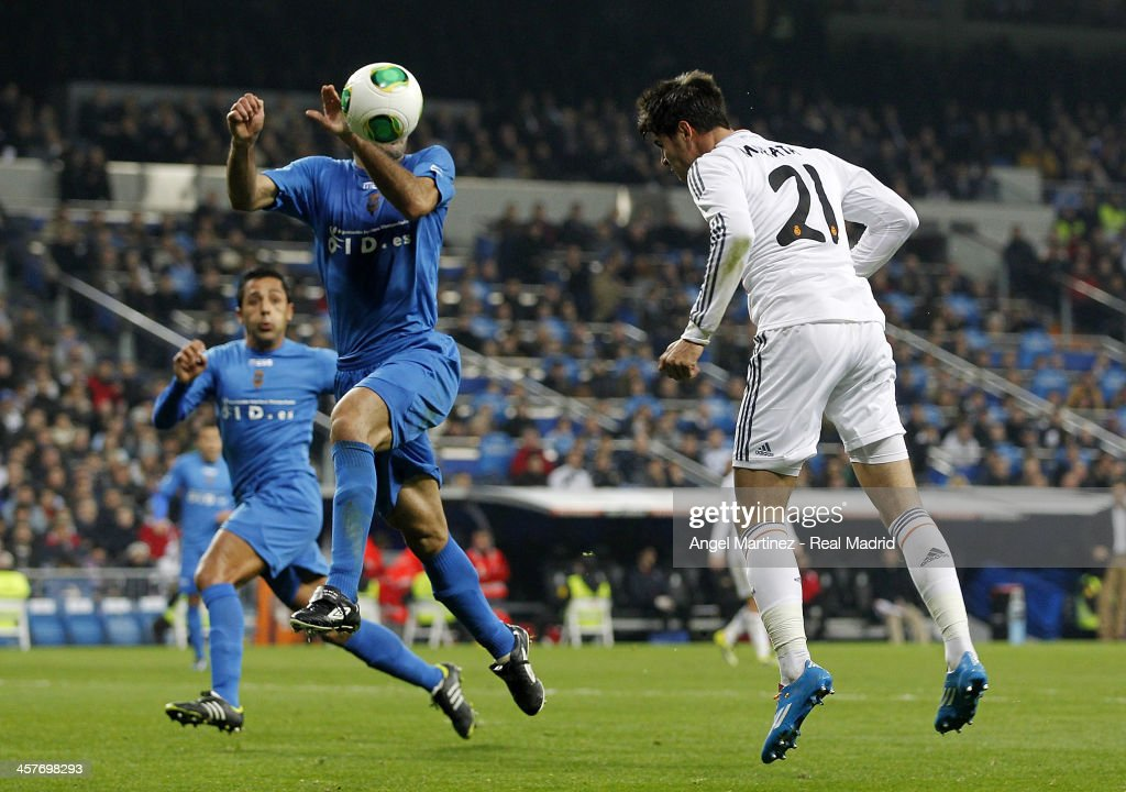 Alvaro Morata of Real Madrid heads the ball against Kike Alcazar of Olimpic de Xativa during the Copa del Rey, round of 32 match between Real Madrid and Olimpic de Xativa at Estadio Santiago Bernabeu on December 18, 2013 in Madrid, Spain.