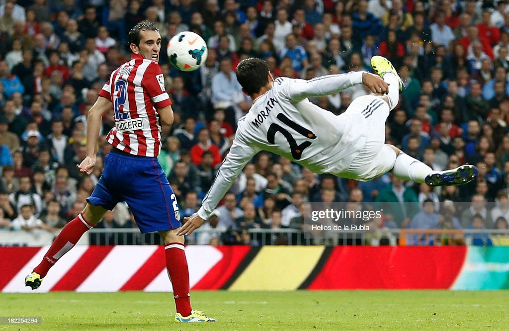 Alvaro Morata (R) of Real Madrid in action against Diego Godín of Atletico de Madrid during the La Liga match between Real Madrid and Club Atletico de Madrid at Estadio Santiago Bernabeu on September 28, 2013 in Madrid, Spain.