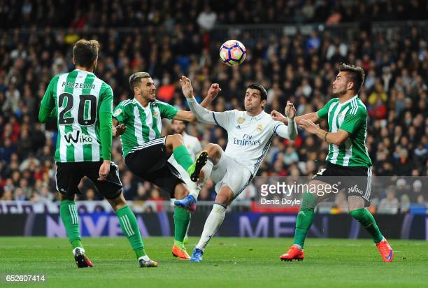 Alvaro Morata of Real Madrid is challenged by Dani Ceballos and Tosca of Real Betis Balompie during the La Liga match between Real Madrid CF and Real...