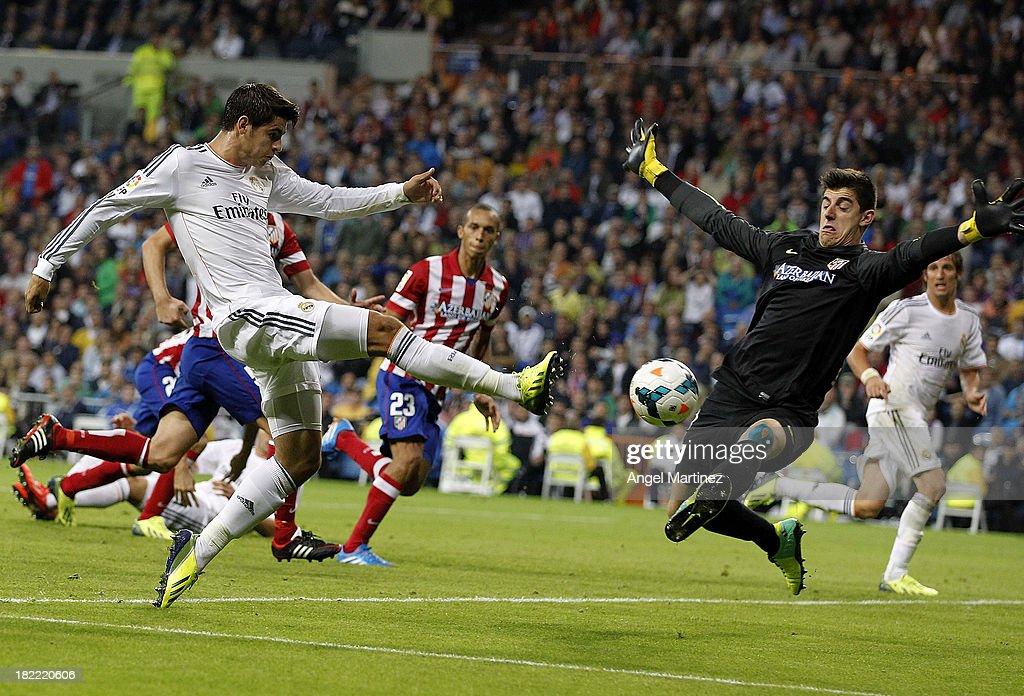Alvaro Morata of Real Madrid shoots on goal past goalkeeper Thibaut Courtois of Atletico de Madrid during the La Liga match between Real Madrid and Club Atletico de Madrid at Estadio Santiago Bernabeu on September 28, 2013 in Madrid, Spain.