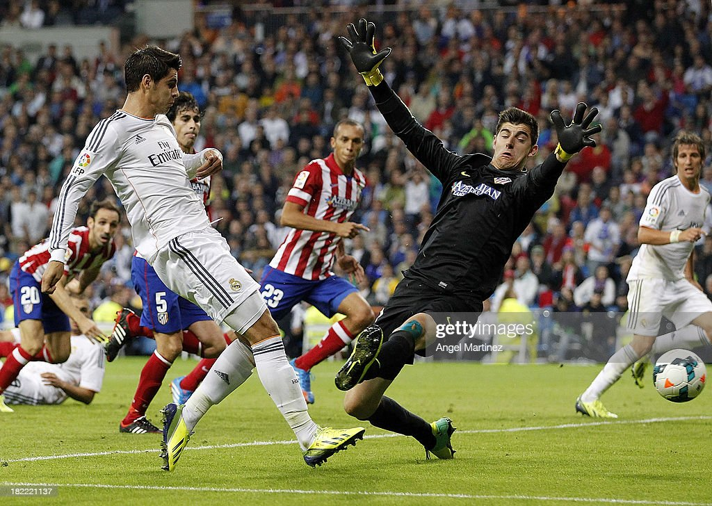 Alvaro Morata of Real Madrid shoots on goal past goalkeeper Thibaut Courtois of Atletico de Madrid during the La Liga match between Real Madrid and Club Atletico de Madrid at Estadio Santiago Bernabeu on September 28, 2013 in Madrid, Spain.