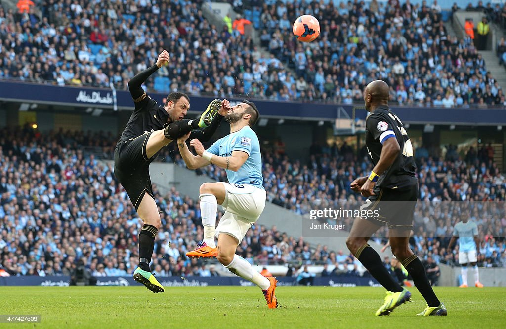 Alvaro Negredo of Manchester City battles with Ivan Ramis of Wigan Athletic during the FA Cup QuarterFinal match between Manchester City and Wigan...