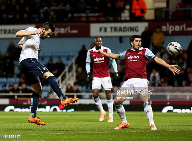 Alvaro Negredo of Manchester City beats James Tomkins of West Ham United to score their first goal during the Capital One Cup SemiFinal Second Leg...