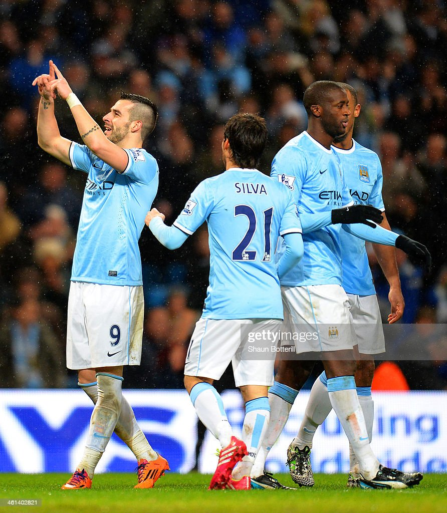 Alvaro Negredo of Manchester City celebrates scoring their fourth goal and his hat trick with team mates during the Capital One Cup Semi-Final first leg match between Manchester City and West Ham United at Etihad Stadium on January 8, 2014 in Manchester, England.