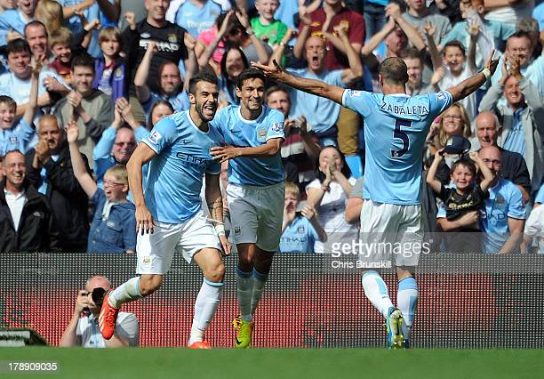 Alvaro Negredo of Manchester City celebrates with teammates Jesus Navas and Pablo Zabaleta after scoring the opening goal of the Barclays Premier...
