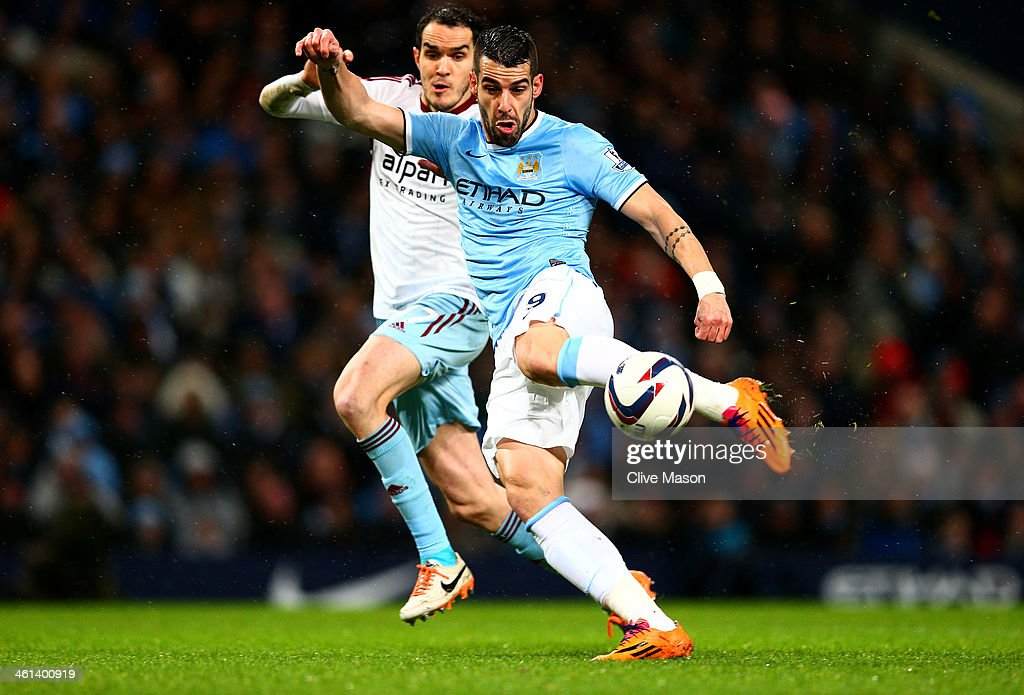 <a gi-track='captionPersonalityLinkClicked' href=/galleries/search?phrase=Alvaro+Negredo&family=editorial&specificpeople=4085785 ng-click='$event.stopPropagation()'>Alvaro Negredo</a> of Manchester City scores the opening goal during the Capital One Cup Semi-Final first leg match between Manchester City and West Ham United at Etihad Stadium on January 8, 2014 in Manchester, England.