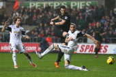 Alvaro Negredo of Manchester City shoots past Chico Flores of Swansea City during the Barclays Premier League match between Swansea City and...