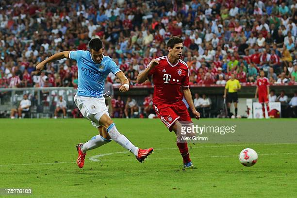 Alvaro Negredo of Manchester scores his team's first goal against Javier Martinez of Muenchen during the Audi Cup Final match between FC Bayern...