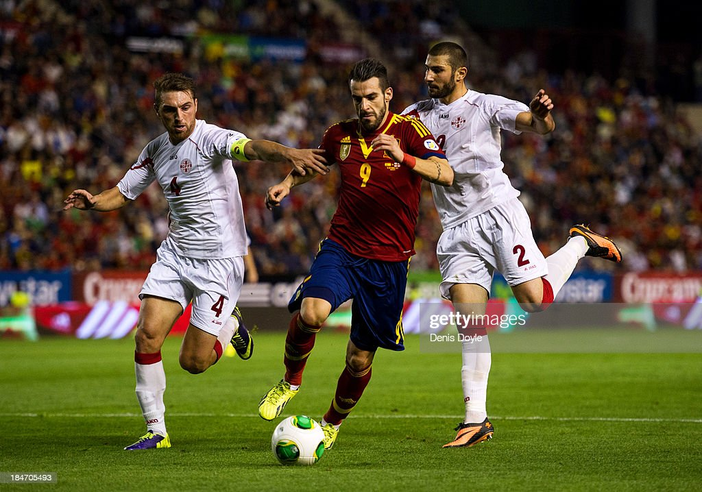 <a gi-track='captionPersonalityLinkClicked' href=/galleries/search?phrase=Alvaro+Negredo&family=editorial&specificpeople=4085785 ng-click='$event.stopPropagation()'>Alvaro Negredo</a> (C) of Spain is challenged by Ucha Lobjanidze (R) and Guram Kashia of Georgia during the FIFA 2014 World Cup Qualifier between Spain and Georgia on October 15, 2013 in Albacete, Spain.