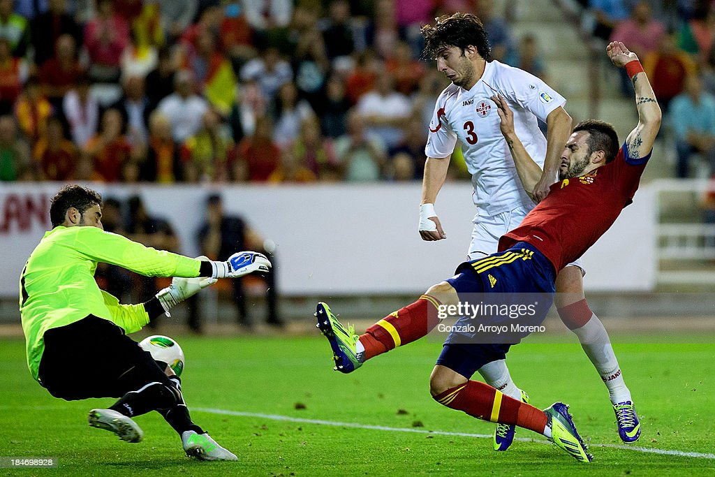 <a gi-track='captionPersonalityLinkClicked' href=/galleries/search?phrase=Alvaro+Negredo&family=editorial&specificpeople=4085785 ng-click='$event.stopPropagation()'>Alvaro Negredo</a> of Spain strikes the ball through goalkeeper Giorgi Loria during the FIFA 2014 World Cup Qualifier match between Spain and Georgia at Carlos Belmonte stadium on October 15, 2013 in Albacete, Spain.