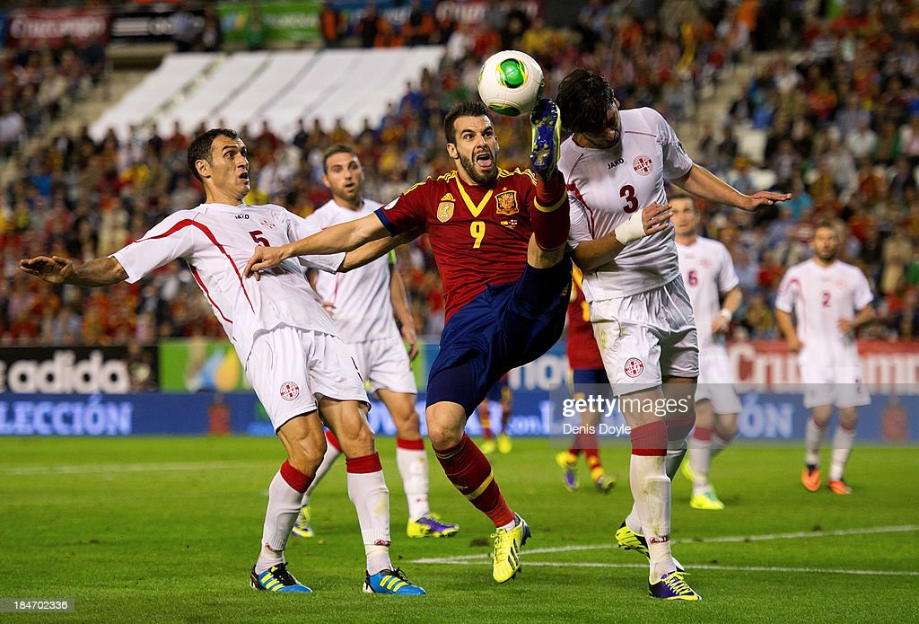 <a gi-track='captionPersonalityLinkClicked' href=/galleries/search?phrase=Alvaro+Negredo&family=editorial&specificpeople=4085785 ng-click='$event.stopPropagation()'>Alvaro Negredo</a> (C) of Spain vies for the ball with Davit Kyrkvelia (L) and Giorgi Khidesheli of Georgia during the FIFA 2014 World Cup Qualifier between Spain and Georgia on October 15, 2013 in Albacete, Spain.