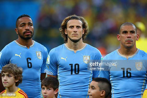 Alvaro Pereira Diego Forlan and Maximilliano Pereira of Uruguay look on during the National Anthem prior to the 2014 FIFA World Cup Brazil round of...