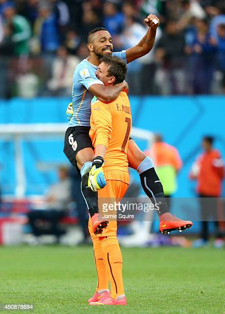 Alvaro Pereira of Uruguay celebrates with goalkeeper Fernando Muslera after their team's first goal during the 2014 FIFA World Cup Brazil Group D...