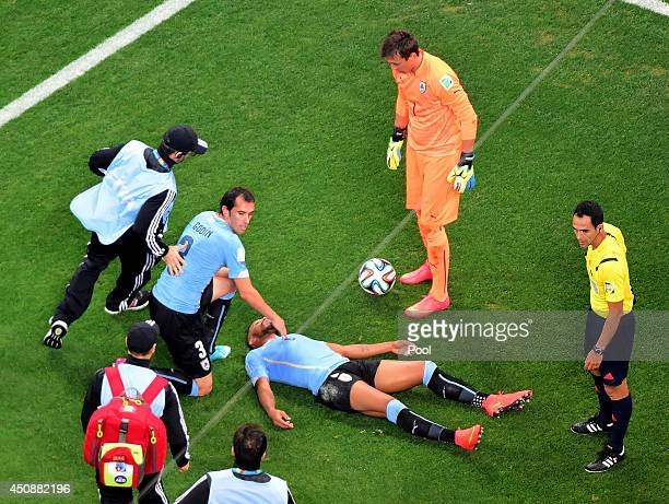 Alvaro Pereira of Uruguay lies on the field after a collision as teammates Diego Godin and Fernando Muslera look on during the 2014 FIFA World Cup...