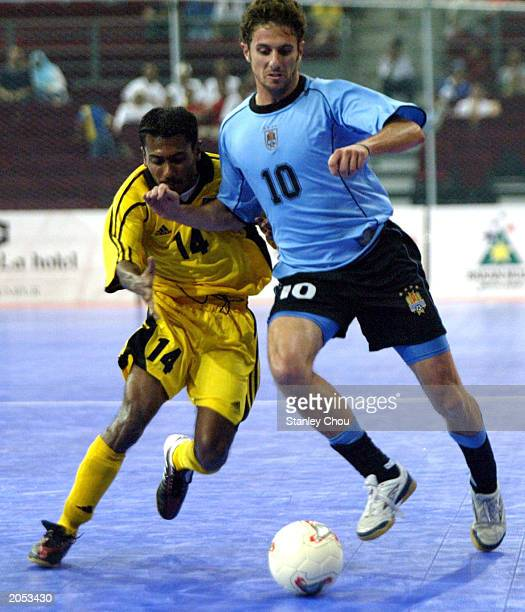 Alvaro Pineiro of Uruguay battles with Mohd Feroz of Malaysia during the 2003 World 5s Futsal Championship between Uruguay and Malaysia on June 03...