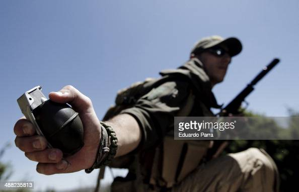 Alvaro Quero from the spanish airsoft team Condenados takes a grenade assault on an enemy position during a simulation of combat in a game of airsoft...