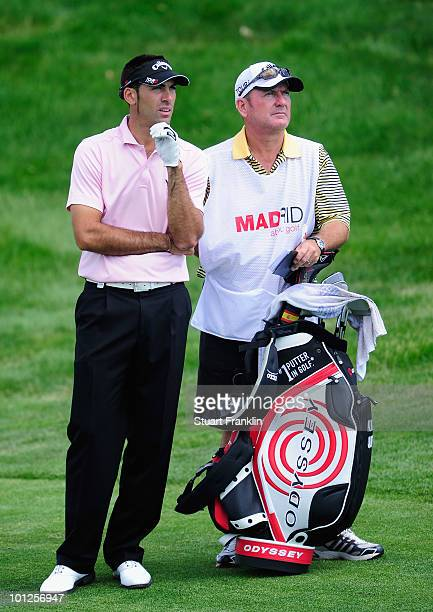 Alvaro Quiros of Spain and caddie Alastair McLean discuss his approach shot on the 16th hole during the third round of the Madrid Masters at Real...