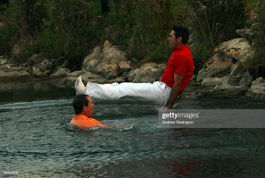 Alvaro Quiros of Spain is thrown into the lake by the 18th green next to his caddie Dave McNeilly after winning the Commercialbank Qatar Masters at...