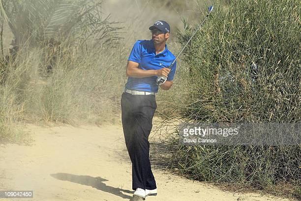 Alvaro Quiros of Spain plays his third shot at the par 4 8th hole during the final round of the 2011 Omega Dubai Desert Classic on the Majilis Course...