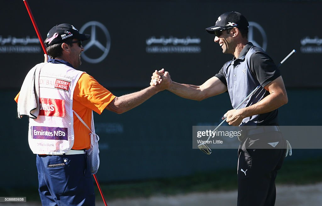 Alvaro Quiros of Spain shakes hands with his caddie on the 18th green during the final round of the Omega Dubai Desert Classic at the Emirates Golf Club on February 7, 2016 in Dubai, United Arab Emirates.